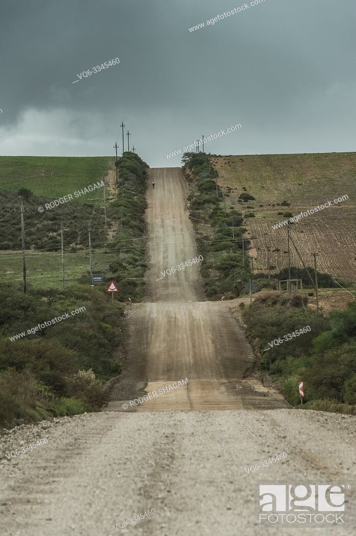 Stock Photo: Mountain bike cyclist travels up hill on a gravel road in the countryside.
