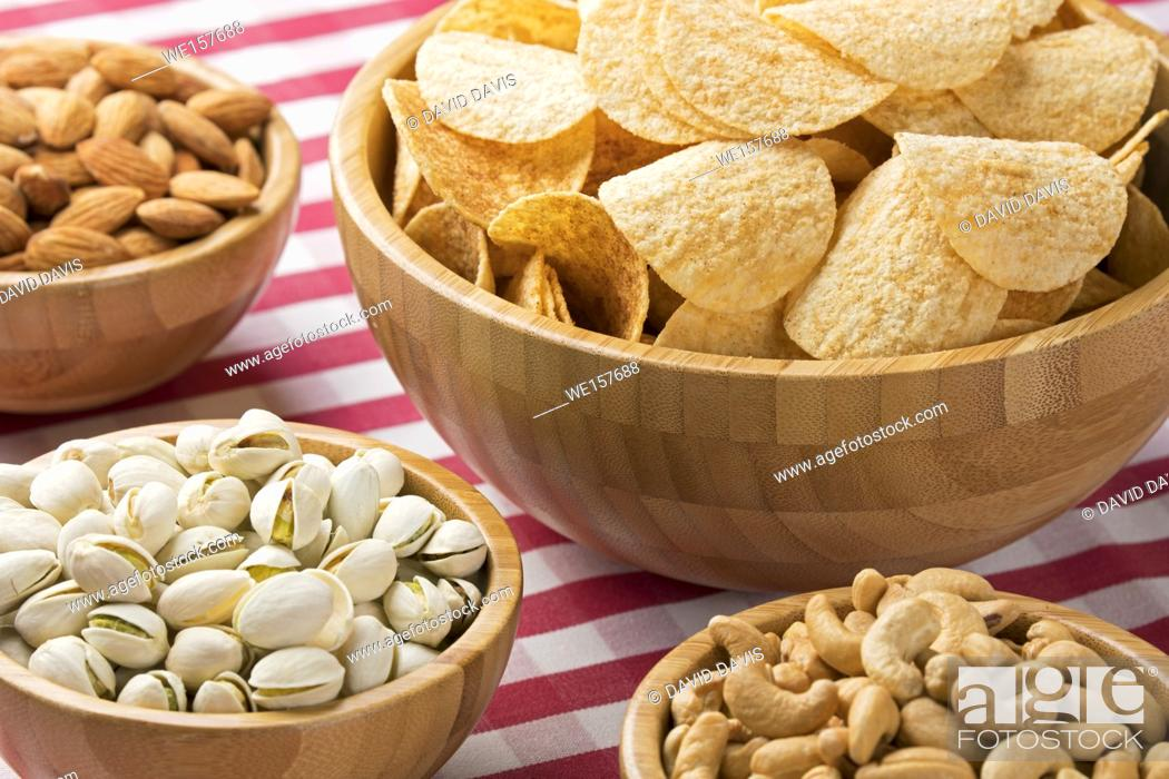 Photo de stock: Close up of party bowls of potato chips, almonds, pistachios, and cashews on a red checkered tablecloth.