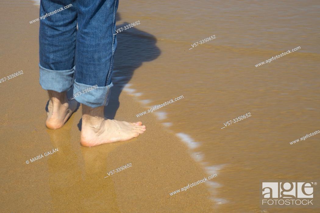 Stock Photo: Man' s legs in the sea shore.
