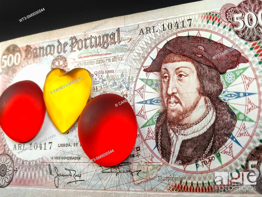 Stock Photo: Money bill with the portrait of Joao II king of Portugal and yellow crystal heart and two red crystal circles on black background.