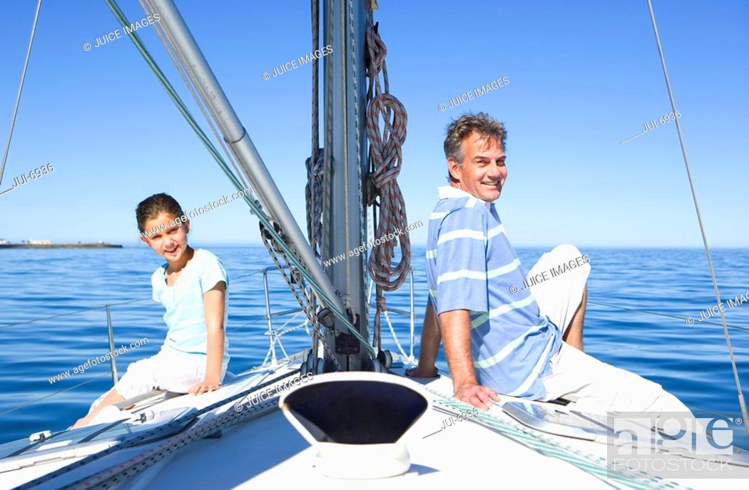 Stock Photo: Father and daughter 8-10 sitting back to back at bow of sailing boat, smiling, side view, portrait.