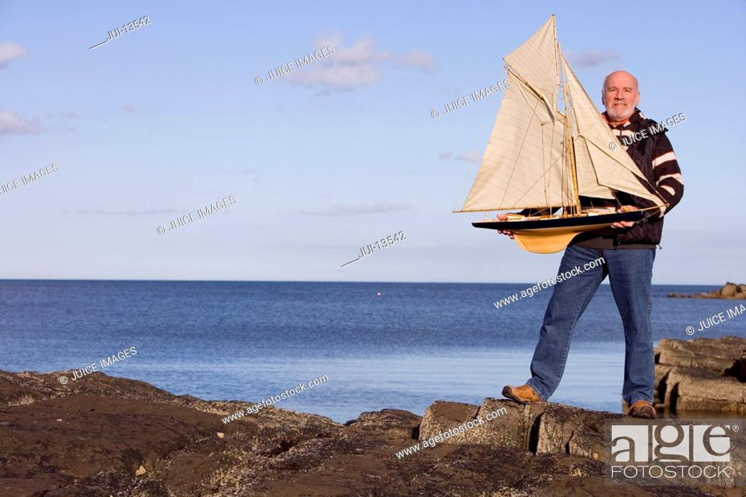 Stock Photo: Senior man holding up model sailboat by sea, smiling, portrait.