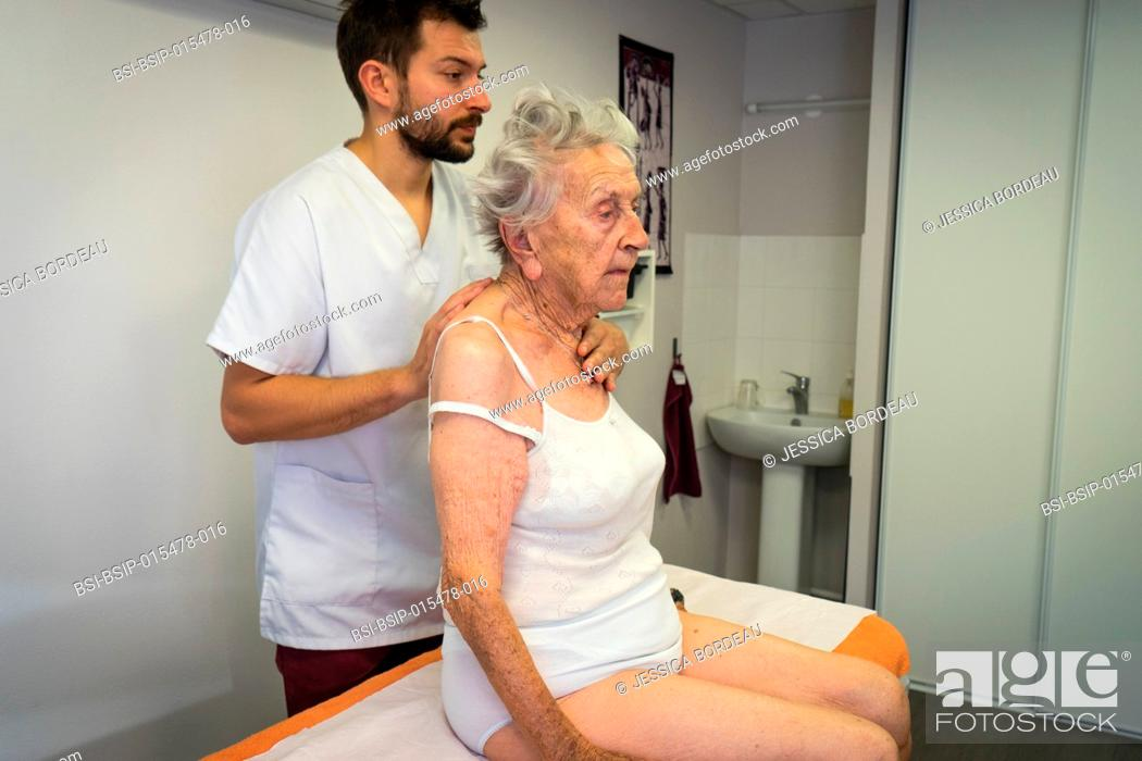 Stock Photo: Reportage in an osteopathy practice in Héyrieux, France. Osteopathy session for a 98-year old woman suffering from back and arthritis pain.