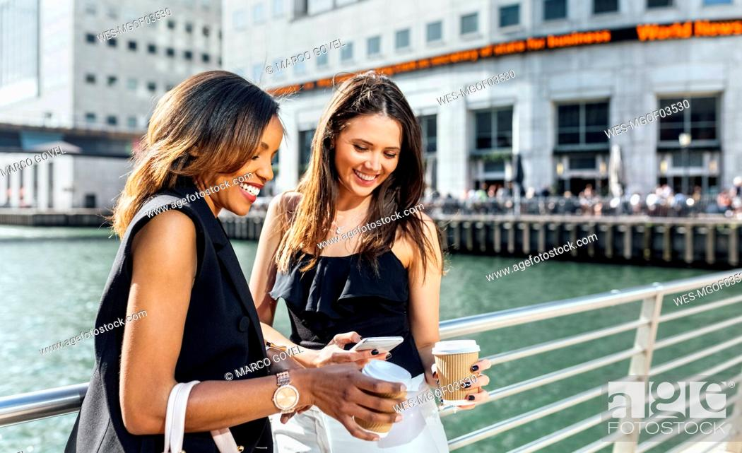 Stock Photo: Two women on a bridge with takeaway coffee and cell phone.