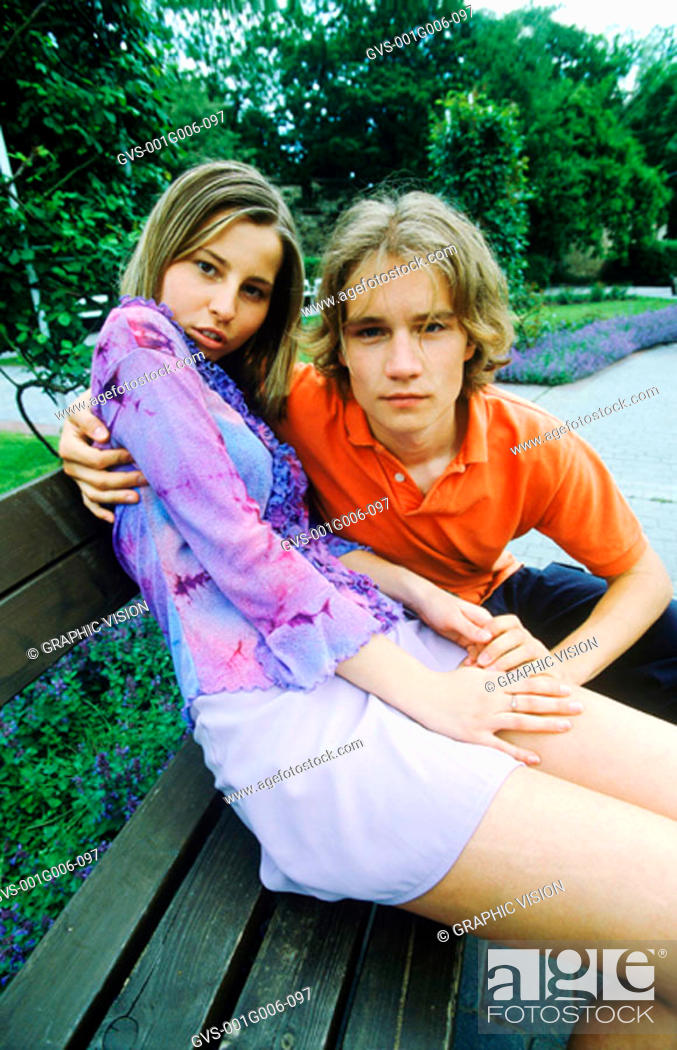 Stock Photo: Portrait of young couple sitting on a park bench.