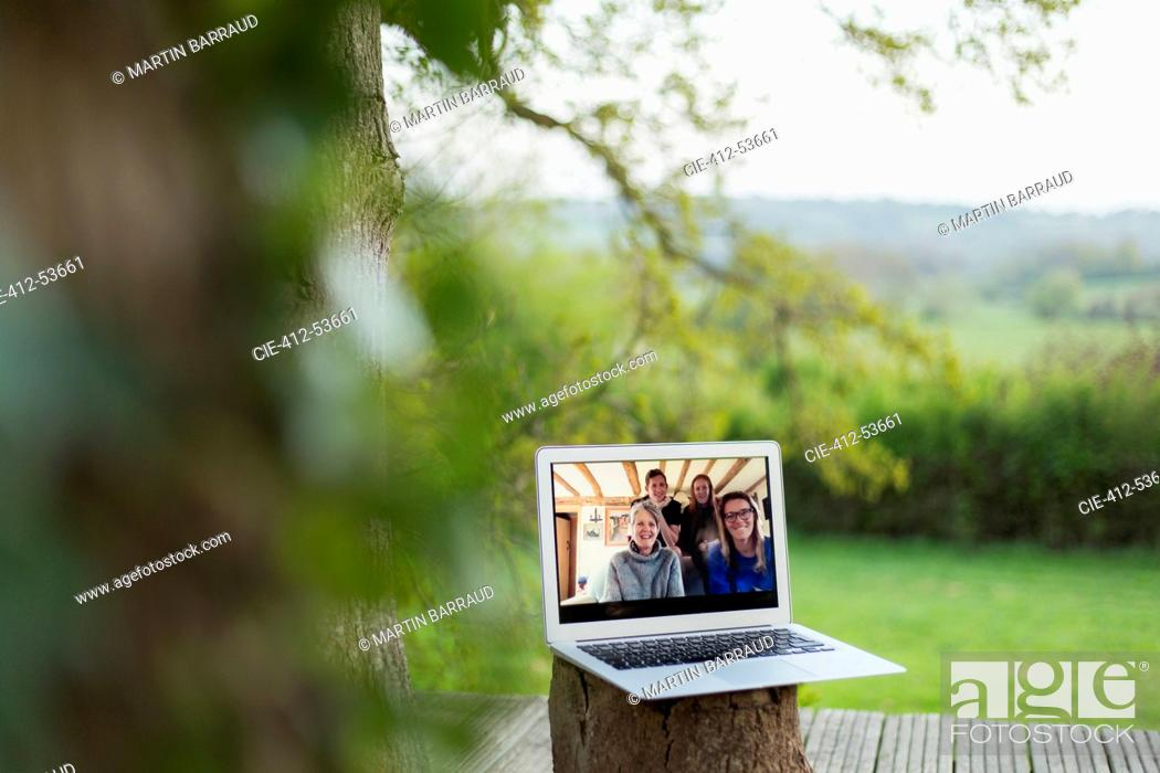Stock Photo: Family video chatting on laptop screen on balcony.