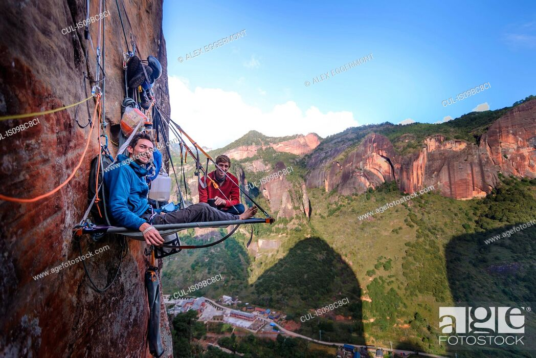 Stock Photo: Portrait of two rock climbers on portaledge, Liming, Yunnan Province, China.