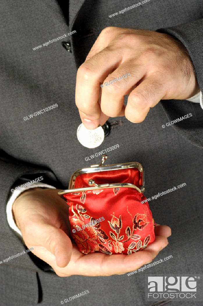 Stock Photo: Mid section view of a businessman putting money into a change purse.