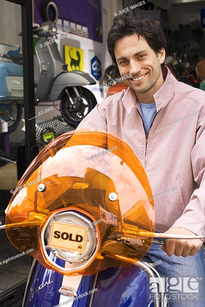 Stock Photo: Man standing outside shop with new scooter, orange sold sticker on headlight, smiling, portrait.