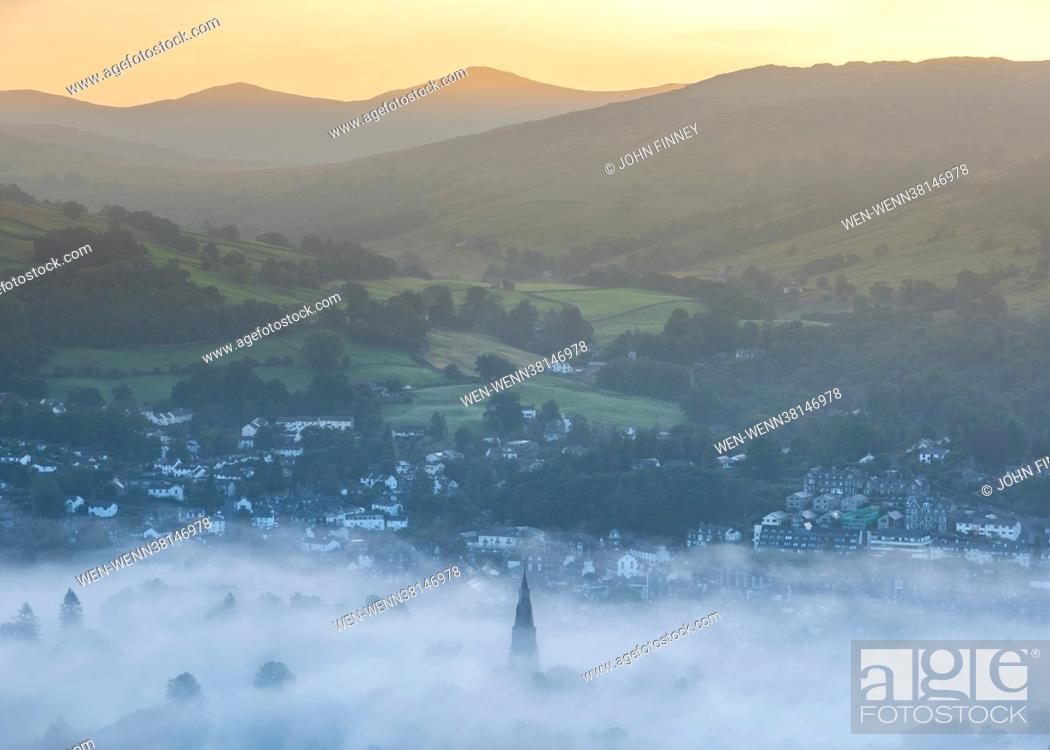 Stock Photo: Sunrise at Lake Windermere with early morning mist and fog sweeping over the landscape. Photographed from Loughrigg Fell, above Clappersgate, near Ambleside.