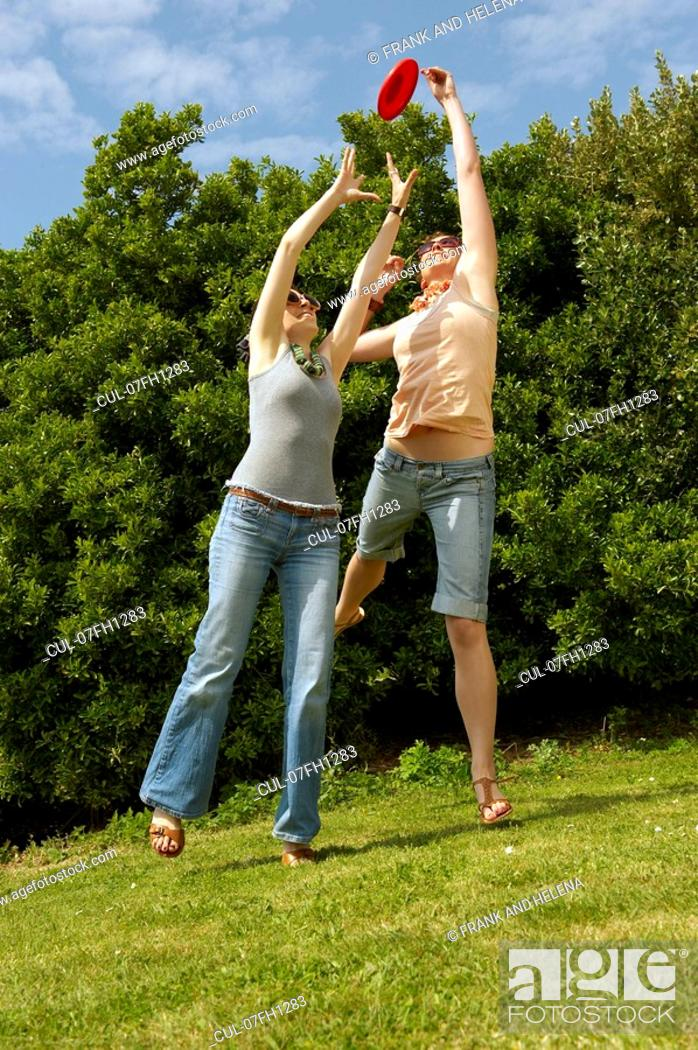 Stock Photo: Two women jumping to catch a frisbee.