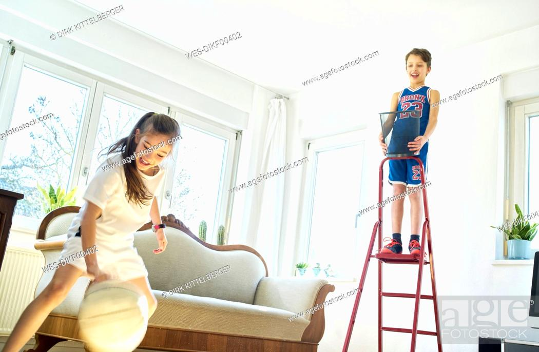 Stock Photo: Boy and girl playing basketball in living room.