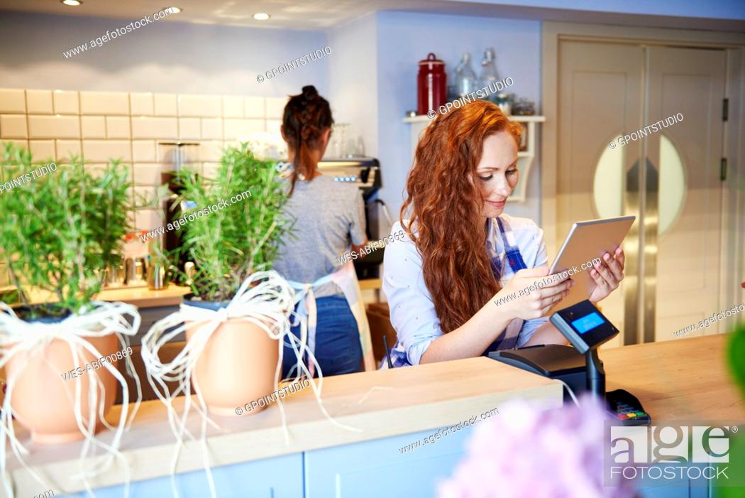Stock Photo: Young woman working in a cafe using tablet at the counter.