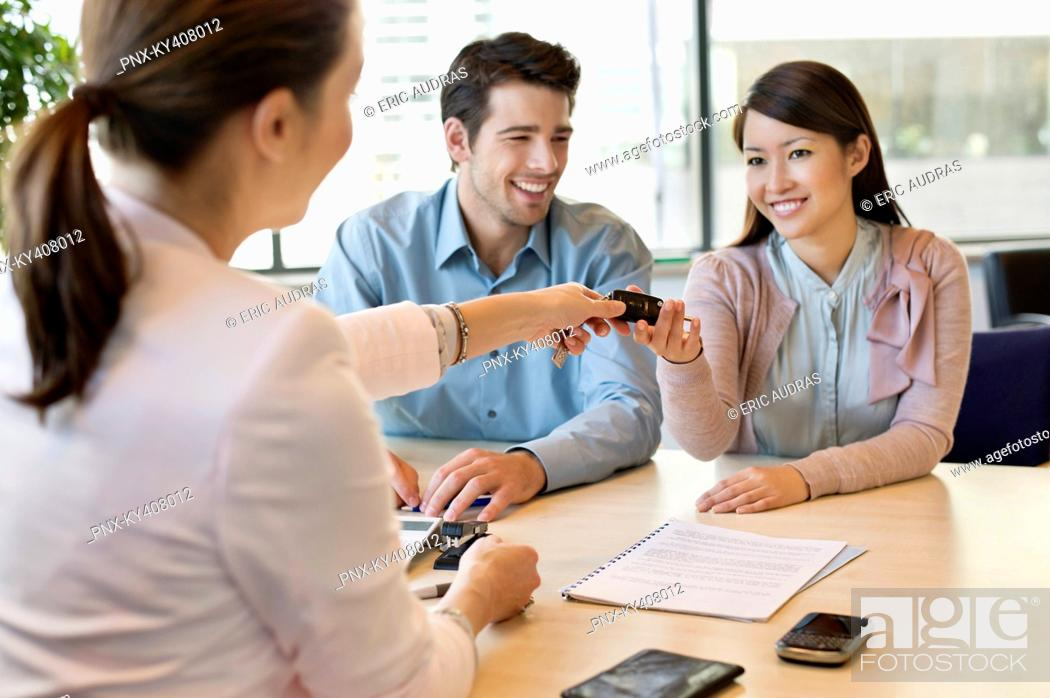 Stock Photo: Couple receiving keys from business executive.