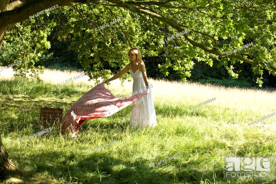 Stock Photo: A young woman laying a picnic blanket on the grass.