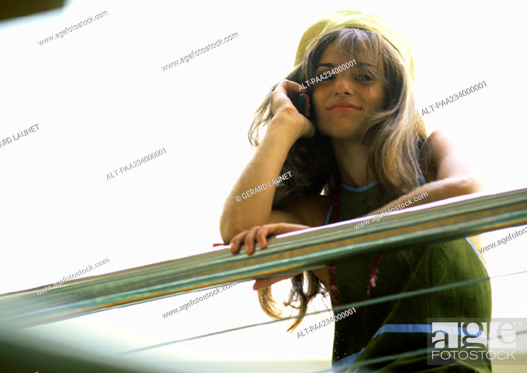 Stock Photo: Woman leaning on arm rail talking on cell phone, low angle view.