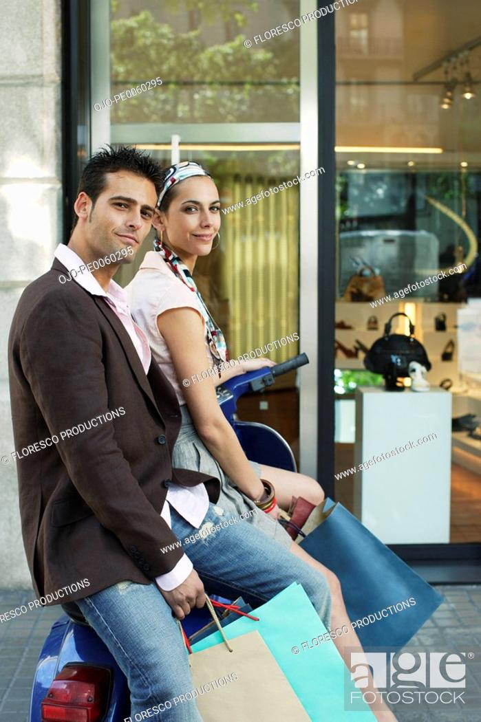 Stock Photo: Couple outdoors on scooter with shopping bags.