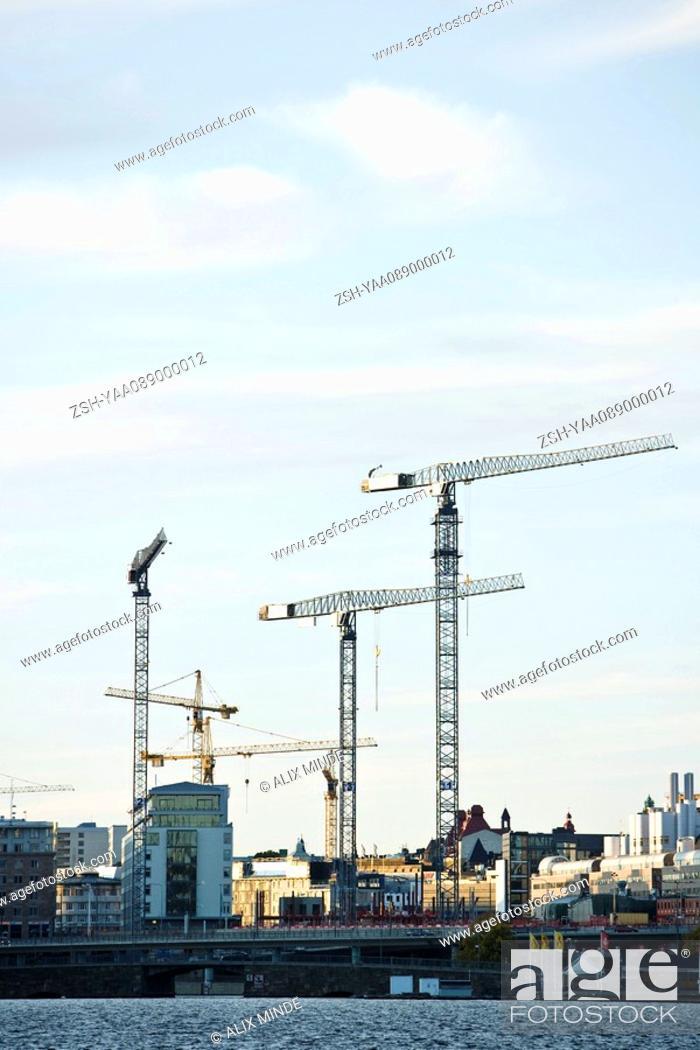 Stock Photo: Sweden, Stockholm, construction cranes along water's edge.