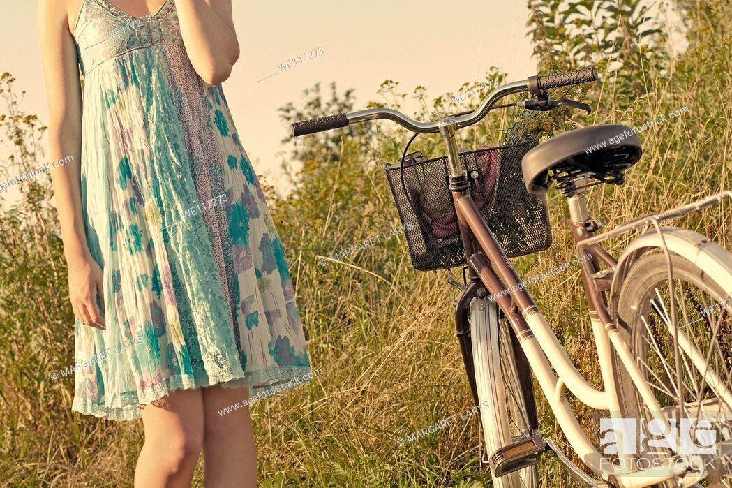 Stock Photo: A young girl in a blue dress with a vintage bike in the meadow, waiting.
