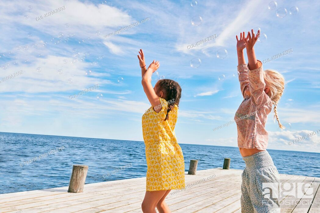 Stock Photo: Two young friends playing on wooden pier, reaching for bubbles.