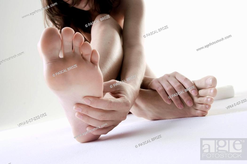 Stock Photo: Close-up of a naked woman touching her toes.