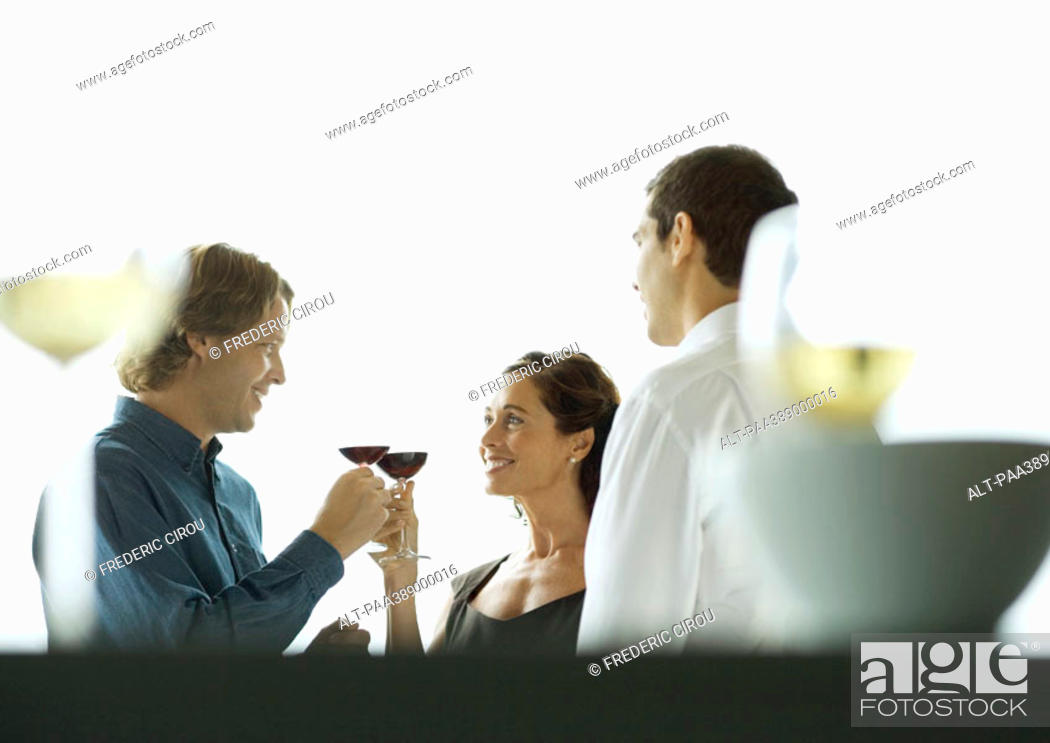 Stock Photo: Man and woman clinking glasses during party.