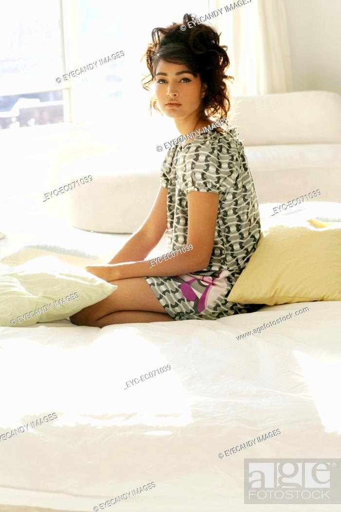 Stock Photo: Young stylish woman sitting on bed.