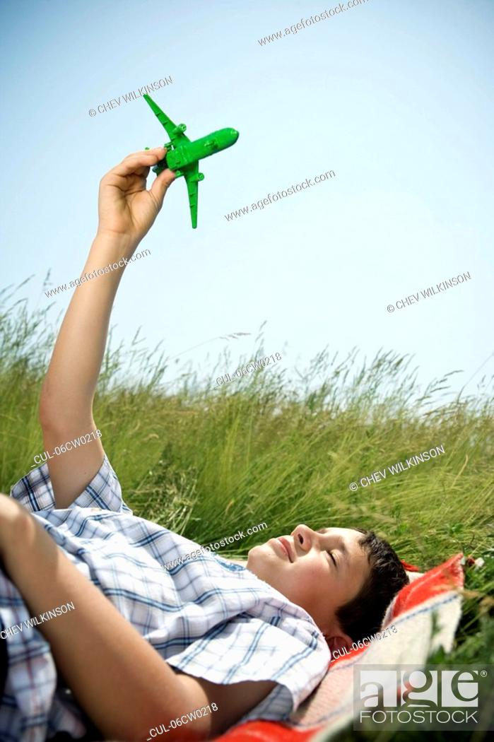 Stock Photo: Boy lying down playing with plane.
