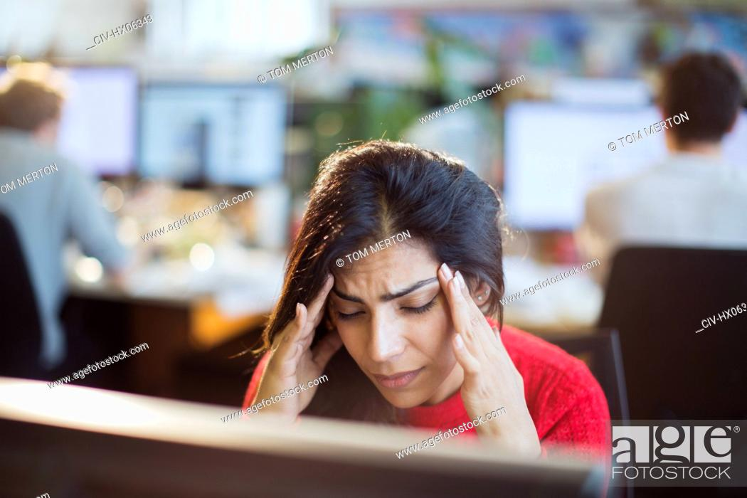 Stock Photo: Stressed businesswoman with head in hands at computer in office.