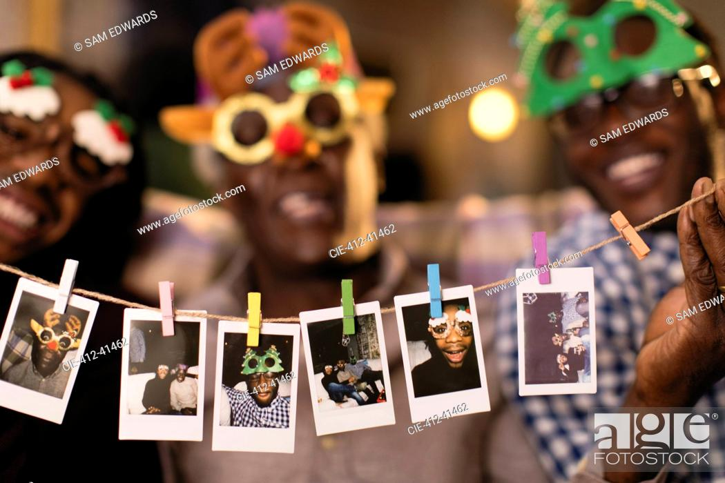 Photo de stock: Portrait playful family in Christmas costume goggles showing instant photos.
