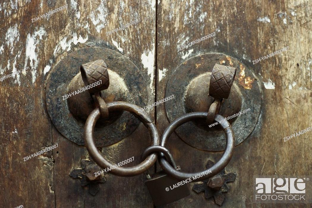 Stock Photo: Old wooden doors, close-up of iron door handles linked by padlock.