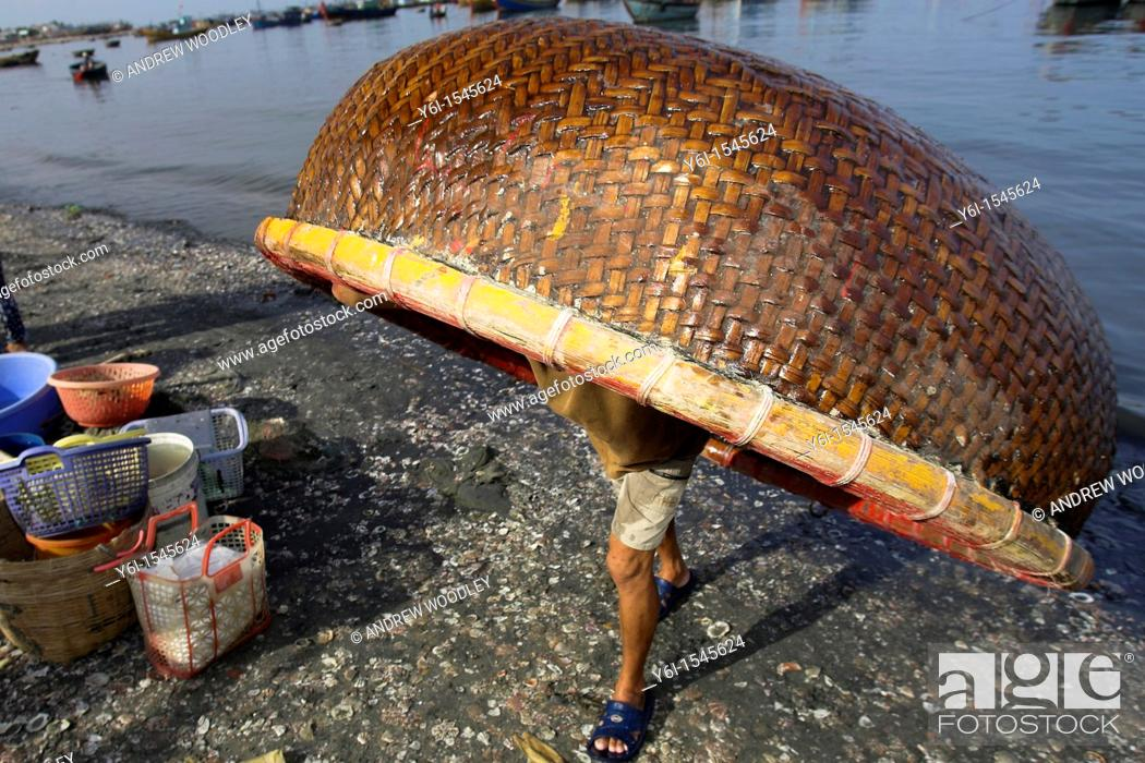 Stock Photo: Fisherman carries small round woven boat on his back up beach Lang Chai fishing village near Mui Ne Vietnam.