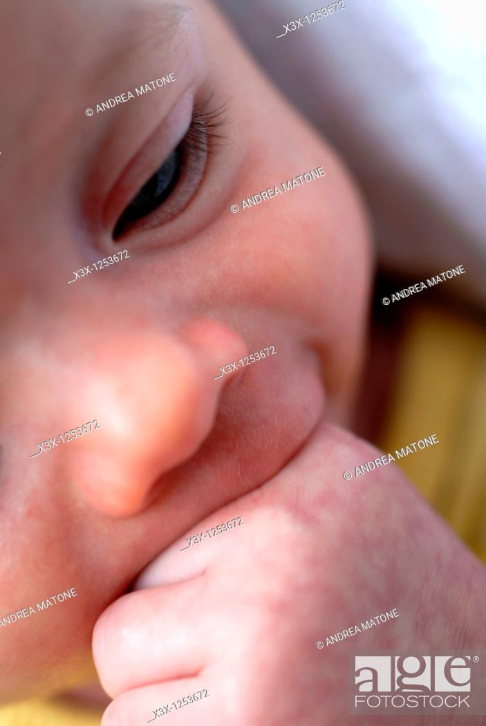 Stock Photo: A new born baby with a hand in mouth.