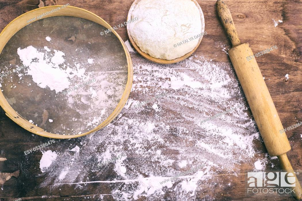 Stock Photo: yeast dough in a wooden bowl and a round vintage sieve with a rolling pin, top view.