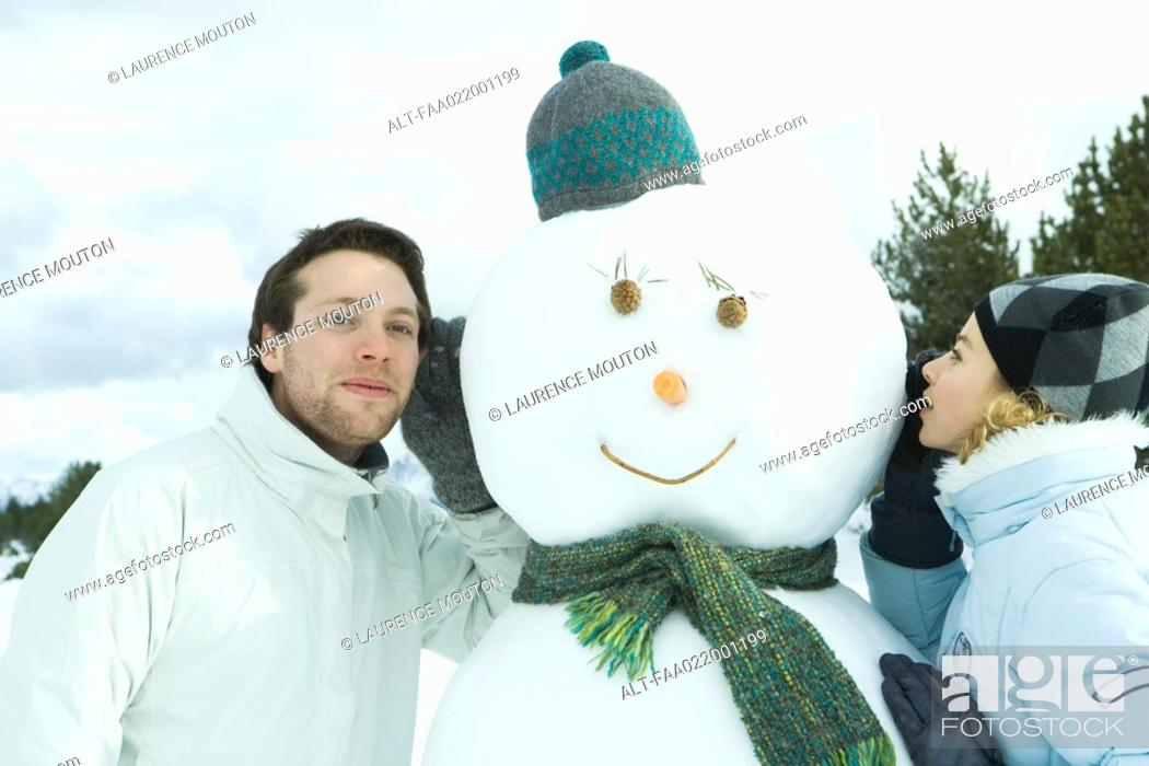 Stock Photo: Brother and sister leaning against snowman, sister whispering, brother listening.