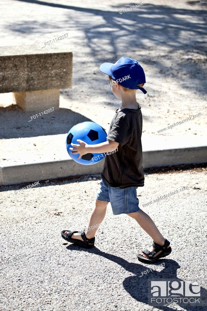 Stock Photo: A young boy walking with a ball.