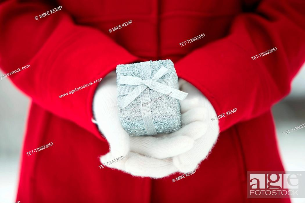 Imagen: Young woman holding Christmas gift.