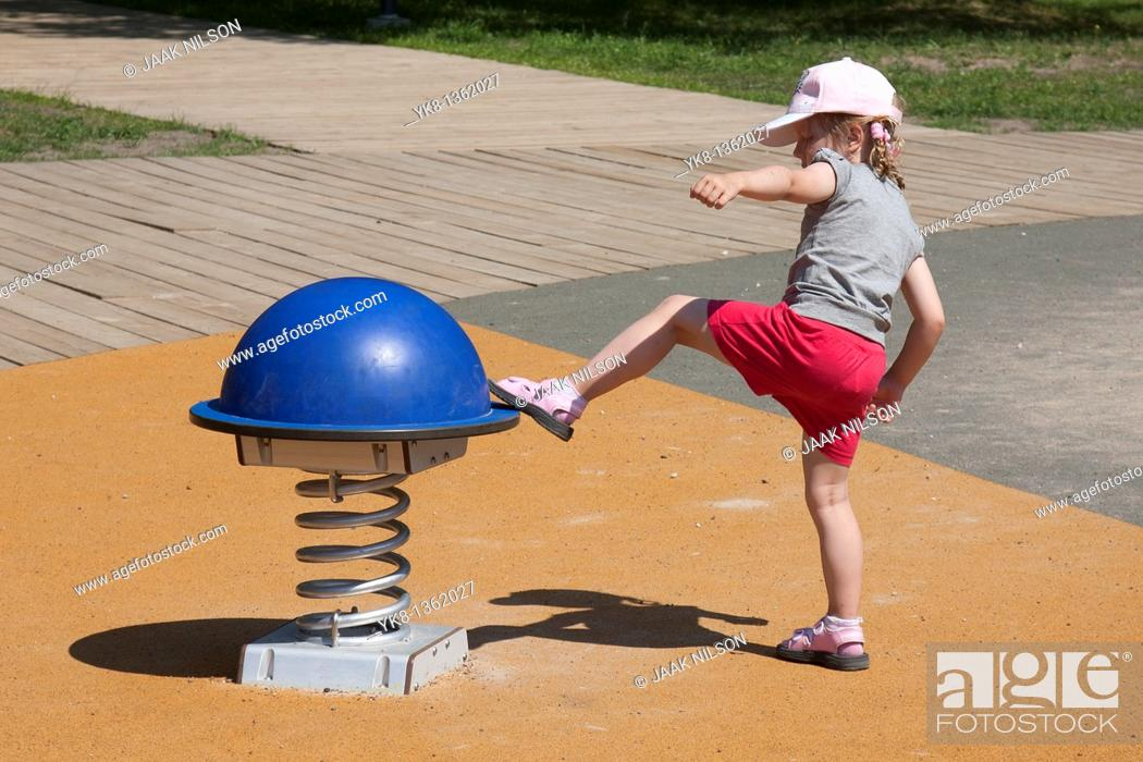 Stock Photo: Four Years Old Girl Kicking Swing at Playground.
