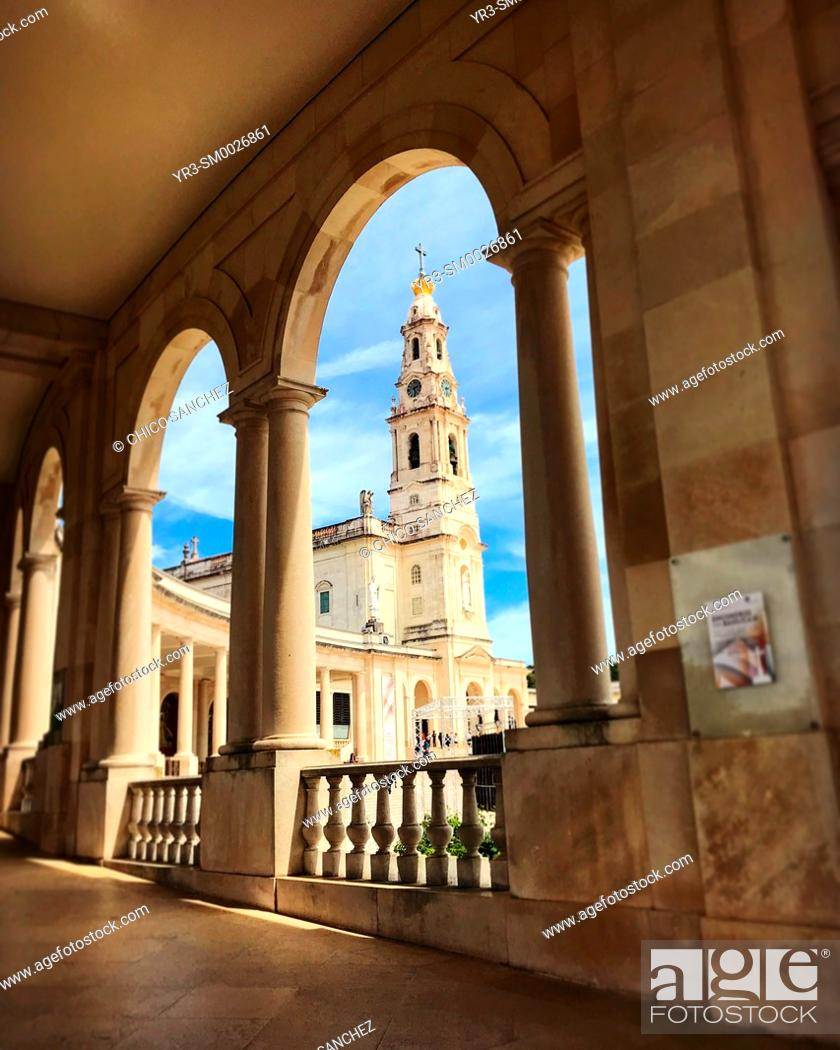 Stock Photo: The bell tower of th Sanctuary of Our Lady of Rosary of Fatima seen between the arches of the sanctuary in Fatima, Portugal.