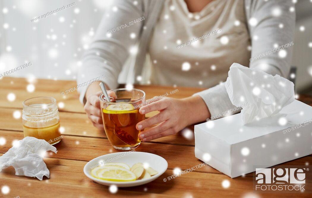 Stock Photo: close up of ill woman drinking tea with lemon.