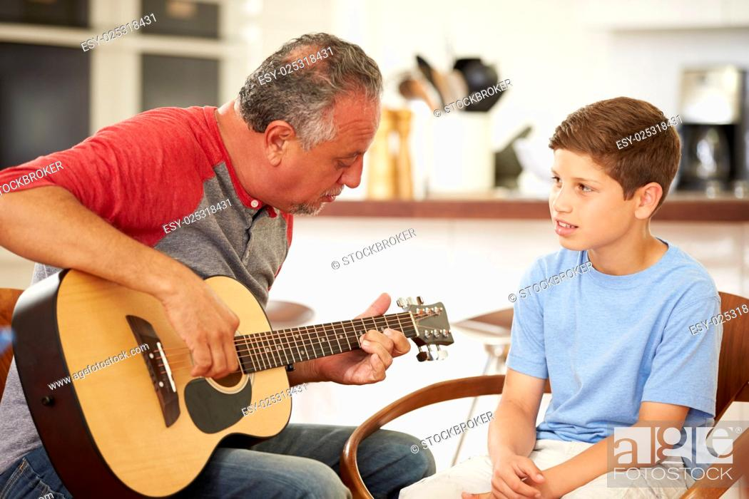 Imagen: Grandfather Teaching Grandson To Play Guitar.