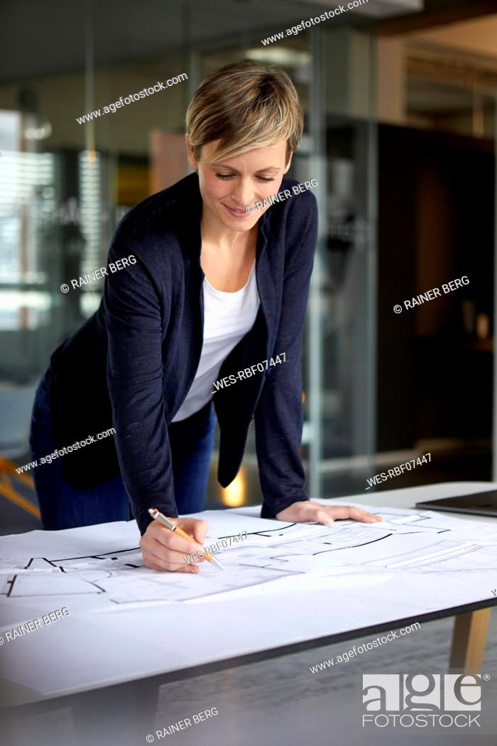 Imagen: Woman working on construction plan in office.