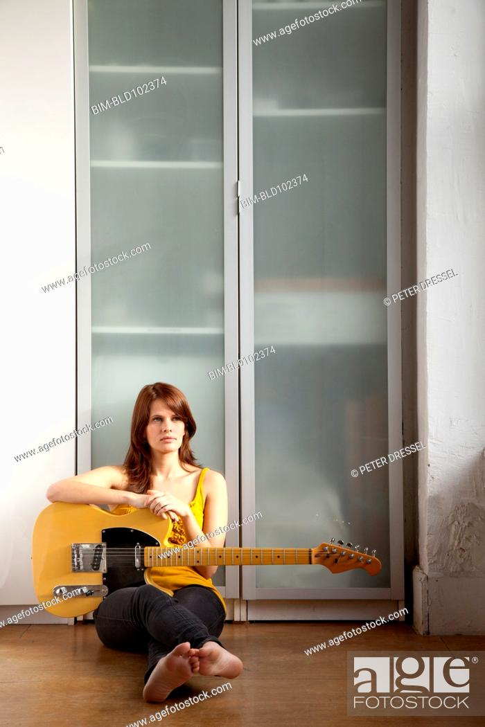 Stock Photo: Woman sitting on floor with guitar.