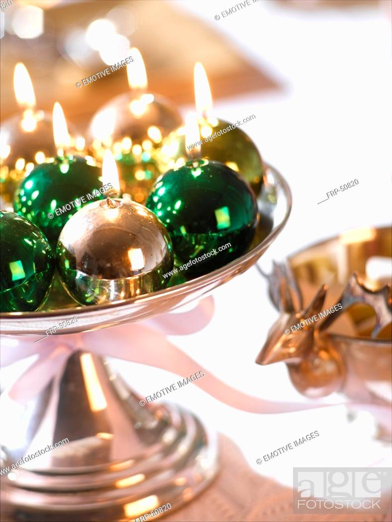 Stock Photo: Glossy Christmas tree ball candles in a silver bowl.