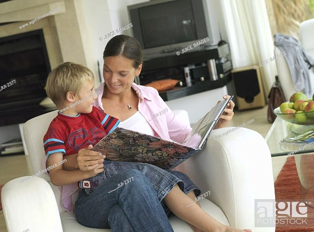Stock Photo: Mother and son 5-7 looking at photo album at home, boy in mother's lap in armchair, smiling tilt.