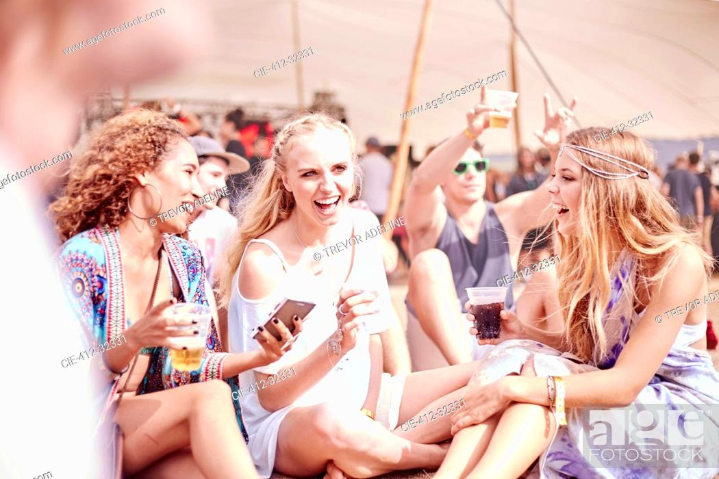 Stock Photo: Young women hanging out drinking at sunny music festival.