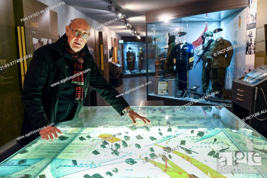 """Stock Photo: 30 September 2019, Hessen, Rasdorf: Berthold Dücker bends over a display case in the border memorial Point Alpha which illustrates the so-called """"""""Fulda Gap""""""""."""