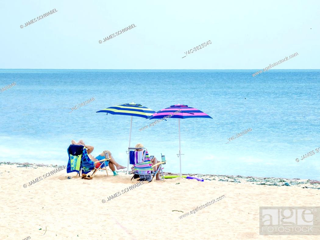 Imagen: Couple relaxing on holiday under a beach umbrella on the Gulf of Mexico beach in Venice Florida USA.