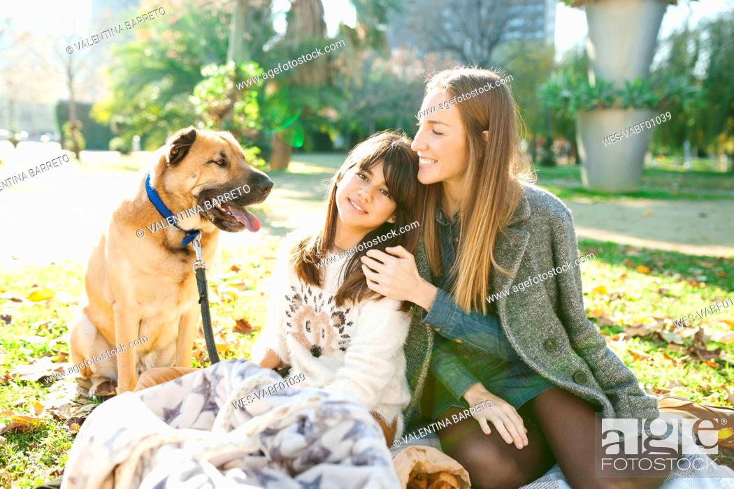 Stock Photo: Mother and daughter with dog in park.