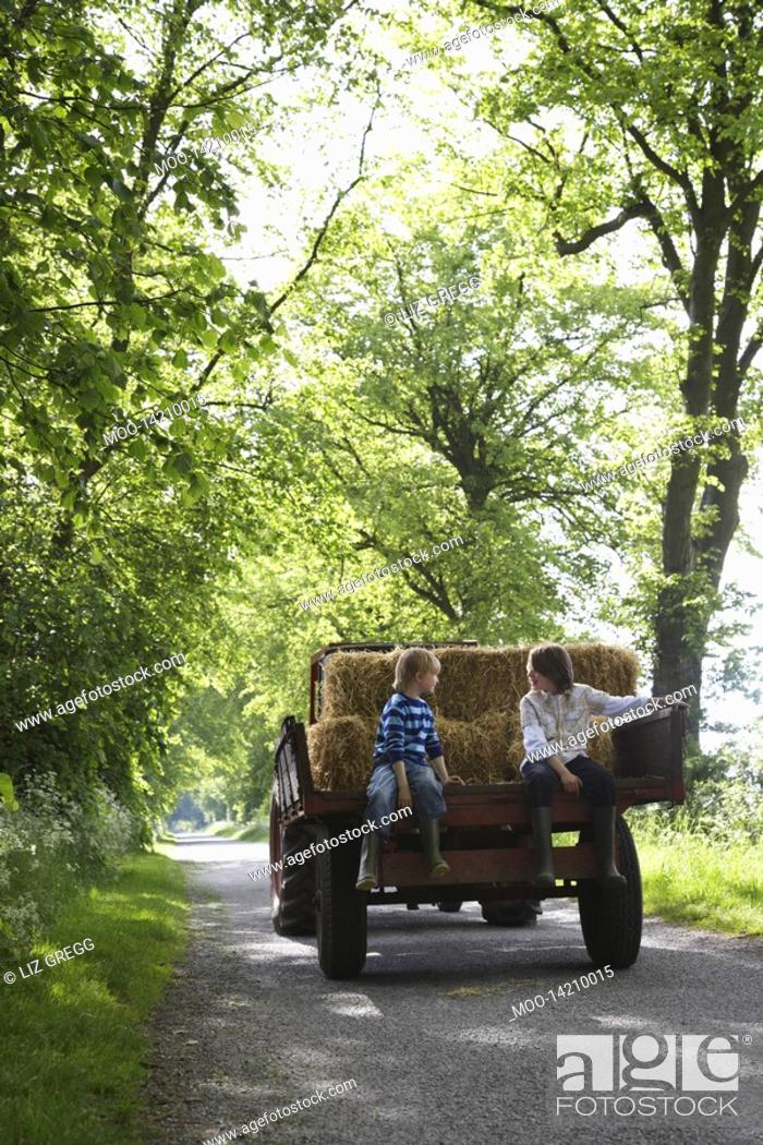 Stock Photo: Two boys 5-6 7-9 sitting on trailer on country lane.